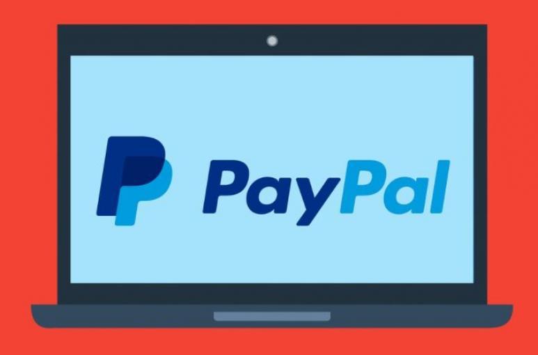 Laptop mit Paypal Logo auf rotem Hintergrund